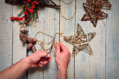 Man's hands do fancy work with Christmas tree decorations Royalty Free Stock Image