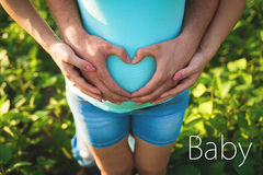 Man's hands embrace a belly of the pregnant woman Stock Photos