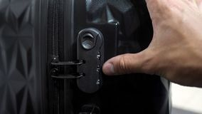 Man`s hands enter password on suitcase combination lock on the suitcase. Man is testing lock. He enters the code to open suitcase combination lock on the stock footage