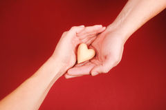 Man's hands are giving little wooden heart to Royalty Free Stock Photo