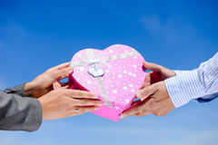 Man's hands giving pink heart shaped box to woman Royalty Free Stock Photo