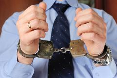 Man's hands in handcuffs before itself. Man holds his hands in handcuffs before itself Royalty Free Stock Photo