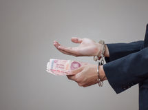 Man's hands in handcuffs and money in his palms Stock Images