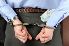 Man's hands in handcuffs with money in his pocket Royalty Free Stock Photos