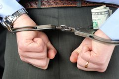 Man's hands in handcuffs with money in his pocket. Man's hands in handcuffs and money in trouser pocket Stock Image