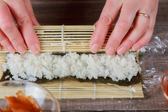 Man& x27;s hands hold bamboo mat. Bamboo mat and cooking board. Chef makes tasty sushi. Royalty Free Stock Photos