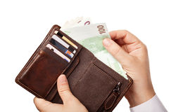 Man's hands holding brown wallet full of m Stock Photo
