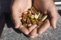 Man's Hands Holding Bullets Royalty Free Stock Image