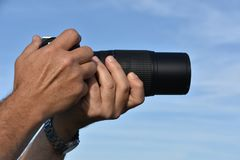 Man`s hands holding the camera with lens royalty free stock photos