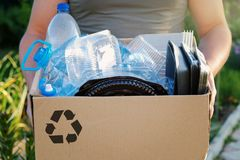 Man`s hands holding a carton with plastic garbage for recycling. Recycle concept. Man`s hands holding a carton with plastic bottles and containers, prepairing royalty free stock images
