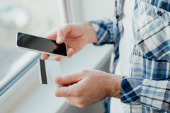Man's hands holding a credit card and phone Royalty Free Stock Photography