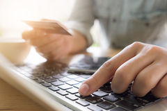 Man's hands holding a credit card and using pc or laptop for onl Royalty Free Stock Photography