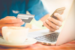 Man's hands holding a credit card and using smart phone Royalty Free Stock Images