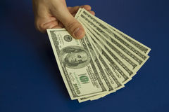 Man`s hands holding dollars on dark blue background Royalty Free Stock Photo