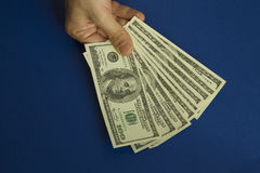 Man`s hands holding dollars on dark blue background Royalty Free Stock Photos