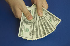 Man`s hands holding dollars on dark blue background Stock Images