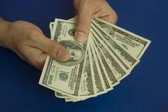 Man`s hands holding dollars on dark blue background Royalty Free Stock Image
