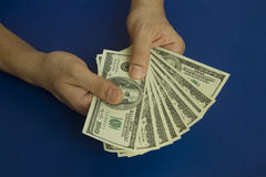 Man`s hands holding dollars on dark blue background Royalty Free Stock Photography