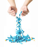 Man's hands holding and dropping a handful of medicine pills Stock Photos