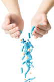 Man's hands holding and dropping a handful of medicine pills Royalty Free Stock Image