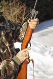 Man`s hands holding a flask with a long gun hunting. Royalty Free Stock Images