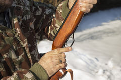 Man`s hands holding a flask with a long gun hunting. Stock Images