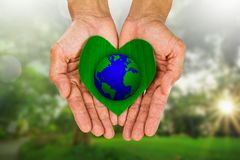 Man& x27;s hands holding heart shaped green leaf with earth on blurred nature background Royalty Free Stock Image