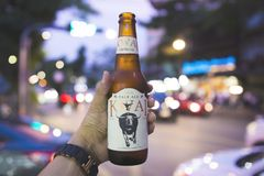 Man`s hands are holding Kwai Beer bottles stock photos