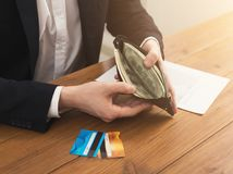 Man`s hands holding open wallet with money. Image of a man`s hands holding open full of money leather wallet with credit cards on the table, copy space Royalty Free Stock Photography