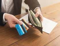 Man`s hands holding open wallet with money. Image of a man`s hands holding open full of money leather wallet with credit cards on the table, copy space Royalty Free Stock Photo