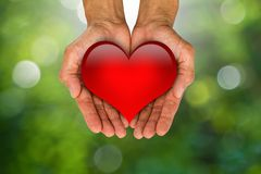 Man& x27;s hands holding red heart on blurred green bokeh background. Man`s hands holding red heart on blurred green bokeh background, helping hand concept Royalty Free Stock Images