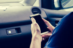 Man's hands holding smart phone inside a car Royalty Free Stock Photos