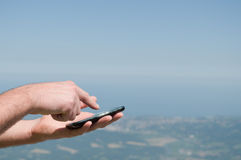 Man's hands holding a smartphone outdoor, and landscape at background Royalty Free Stock Images