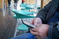Empty cafeteria. Man`s hands holding a smartphone. young man sitting in a coffee shop with green chairs Stock Photo