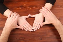 Man's hands holding woman's hands. On wooden table royalty free stock photography