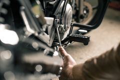 Man`s hands holding wrench. Fixing motorcycle concept. Close up of hand with wrench near the motorcycle Royalty Free Stock Photos