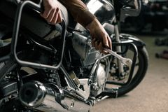 Man`s hands holding wrench. Fixing motorcycle concept. Close up of hand with wrench near the motorcycle Royalty Free Stock Images