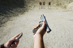 Man's Hands Loading Gun At Firing Range Royalty Free Stock Images