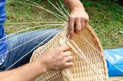Man's hands making a wicker basket. Stock Photo