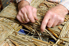 Man's hands making a wicker chair Royalty Free Stock Photo