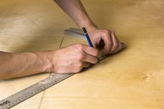 Man`s hands marking measurement on plywood board with a pencil and ruler royalty free stock photography