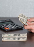 Man's hands with money and calculator Royalty Free Stock Image