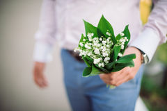 Man's hands with nosegay of lily  the valley. Man's hands with nosegay of lily of the valley give a bouquet of flowers Royalty Free Stock Images