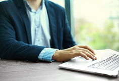 Man's hands on notebook computer, business person at workplace Stock Photography
