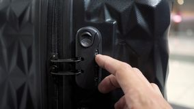 Man`s hands open suitcase combination lock on the suitcase. Man enters the code to open suitcase combination lock on the suitcase and presses the button, hands stock video