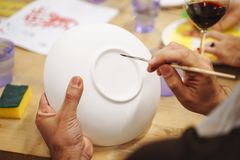 Man`s hands painting a ceramic plate in an art Studio. stock photo