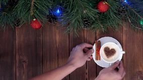 Man`s hands pick up a gift and coffee from the table, a wooden background, a gift for the new year, New Year`s holidays stock video footage