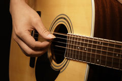 Man's hands playing acoustic guitar Stock Photos