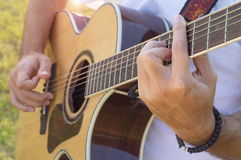 Man's hands playing acoustic guitar outdoors. Man's hands and fingers playing acoustic guitar in the field Stock Images