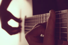 Man`s hands playing on classical guitar against a background of. White light toned,  contrast image. focus on neck Stock Photography